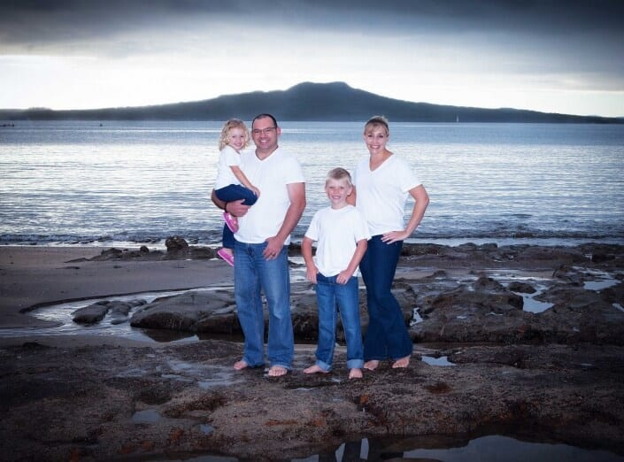 Family portrait at Castor Bay beach with Rangitoto Island
